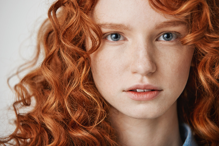 Close up of beautiful natural ginger girl with freckles looking at camera. White background.