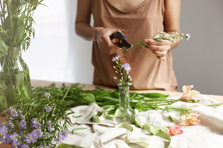 Close up of young female florist cutting stem of flower at workplace over white wall.