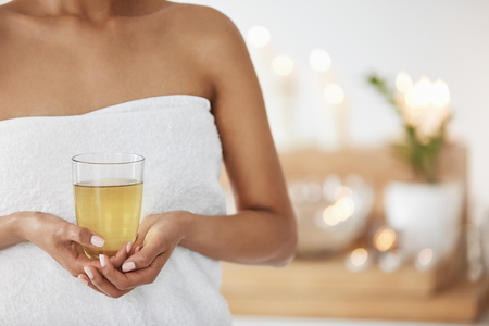 Close up of young girl in towel holding glass with green tea in spa salon.