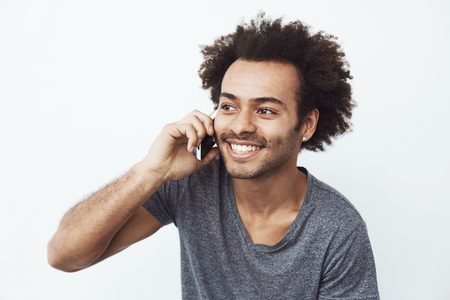 Cheerful african man smiling speaking on phone over white background. Stock Photo