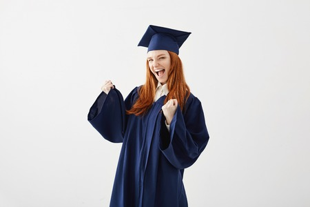 Happy graduate girl in mantle rejoicing laughing smiling over white background. Фото со стока