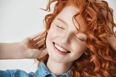 Close up of beautiful redhead young girl smiling with closed eyes. White background.