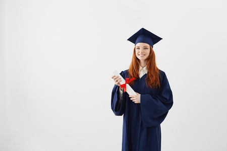 Happy ginger graduate girl in cap and mantle smiling holding diploma. Copy space. Standard-Bild