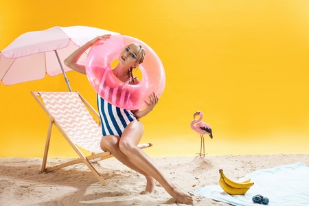 Nice young woman in beach outfit holds pink swimming ring