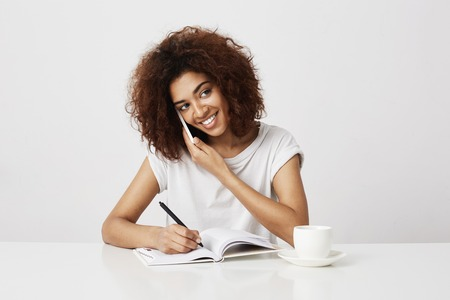 African businesswoman smiling talking on phone at workplace. White background.