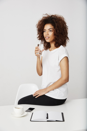 African girl holding glass of water sitting on table over white background. Stock Photo