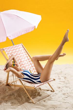 smoky black: Woman sunbathing under umbrella at beautiful beach and enjoying moment