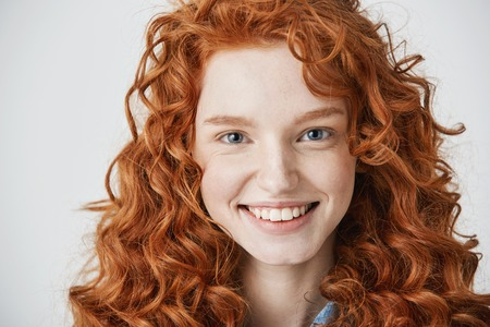 Close up of redhead beautiful girl with freckles smiling looking at camera over white background.