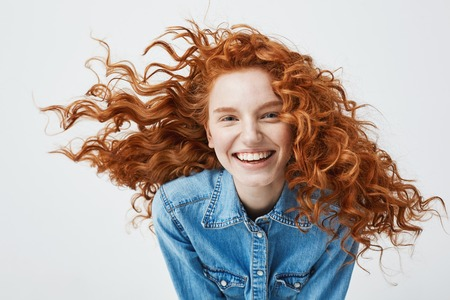 Portrait of beautiful cheerful redhead girl with flying curly hair smiling laughing looking at camera over white background.