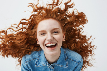Pretty cheerful redhead girl with flying curly hair smiling laughing looking at camera over white background.