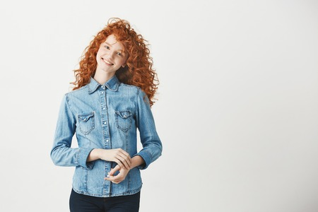 Beautiful redhead girl smiling looking at camera over white background. Copy space. Stock Photo
