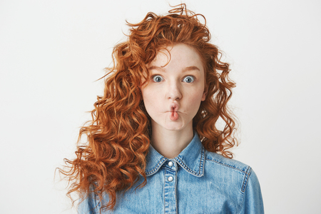 Cute young girl with foxy curly hair making funny face over white background. Copy space.