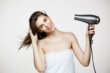 salud sexual: Tender brunette beautiful girl in towel drying hair smiling looking at camera over white bakground. Beauty spa and cosmetology.