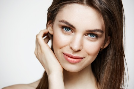Naked young beautiful girl with natural make up smiling looking at camera over white background. Cosmetology and spa. Facial treatment. Banque d'images