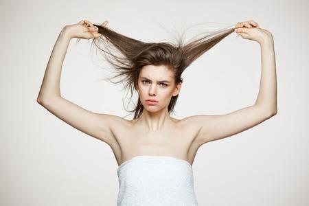 흰색 배경 위에 머리를 만지고 카메라를 찾고 수건에 재미 있은 불쾌 한 어린 소녀. 아름다움 스파와 화장품 개념입니다.