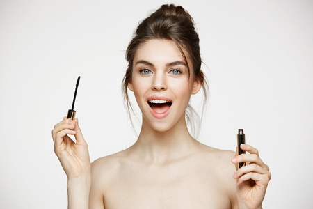 mouth opened: Beautiful surprised girl with perfect clean skin looking at camera with opened mouth holding mascara over white background. Facial treatment.