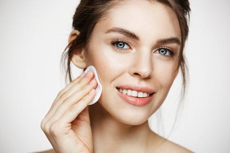 Cute bella faccia di pulizia della ragazza bruna naturale con la spugna di cotone sorridendo guardando la fotocamera su sfondo bianco. Cosmetologia e spa.