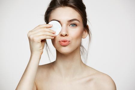Bella ragazza bruna con la pelle pulita perfetta nascondendo dietro la spugna di cotone sorridendo guardando la fotocamera su sfondo bianco. Cosmetologia e spa.