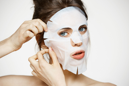 Young girl with facial mask looking at camera over white background. Cosmetic procedure. Beauty spa and cosmetology.