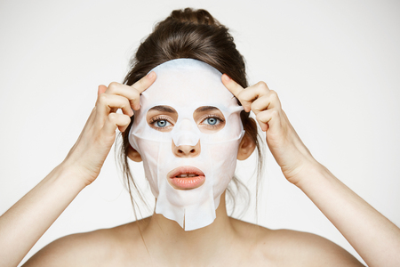 Young girl with facial mask looking at camera over white background. Cosmetic procedure. Beauty spa and cosmetology. Stock Photo - 80390135