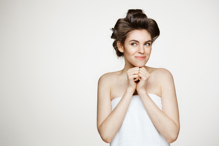 Portrait of young beautiful girl in hair curlers and towel smiling posing over white background. Cosmetology and spa. Stock Photo