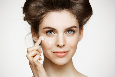 Young beautiful brunette girl in hair curlers smiling looking at camera creaming face over white background. Facial treatment. Beauty health and cosmetology.