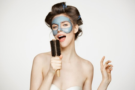 Portrait of young funny girl in hair curlers and facial mask singing in comb over white background. Beauty and skincare concept.
