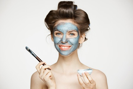 Young beautiful nude girl in hair curlers looking at camera covering face with mack. Facial treatment. Beauty cosmetology and spa.