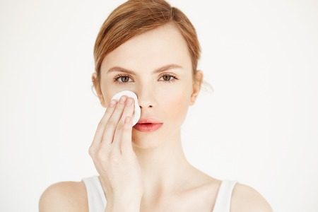 Beautiful natural blonde girl cleaning face with cotton sponge looking at camera over white background. Cosmetology and spa.