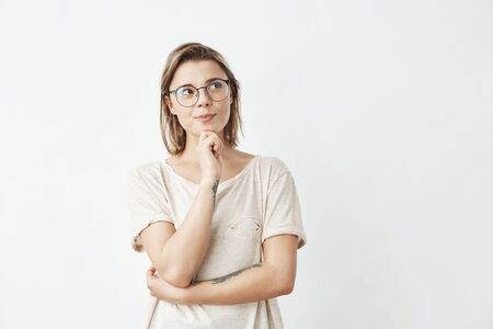 Young beautiful girl in glasses thinking looking in side over white background. Stock Photo