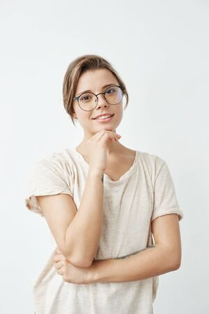 Young tender pretty girl in glasses smiling looking at camera holding hand on chin over white background.