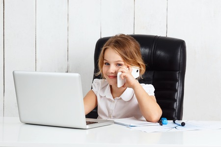 Young beautiful girl speaking phone at working place in office.