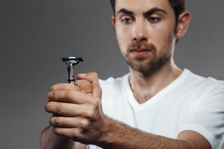 bristles: Young handsome man looking at shaver over grey background. Stock Photo