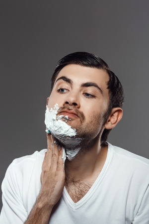 bristles: Man applying cream for shave on face over grey background.