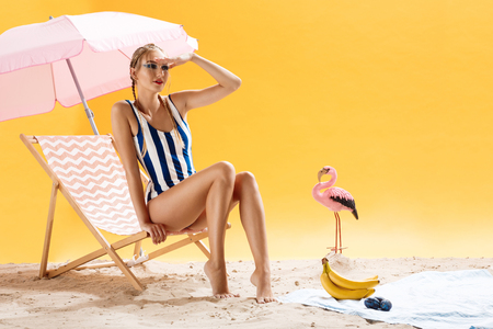 Beautiful young woman wearing striped swimsuit. Isolated over yellow background