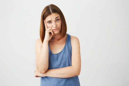 displeased: Portrait of displeased young brunette girl looking at camera with finger on temple thinking over white background. Stock Photo