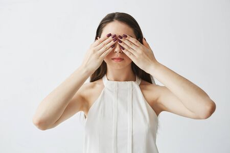 Portrait of young brunette girl covering eyes with hands over white background.