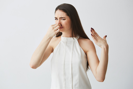 Young brunette girl closing covering nose over white background. Bad smell.