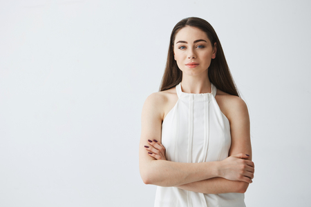cheeful: Portrait of young beautiful businesswoman looking at camera with crossed arms over white background. Stock Photo