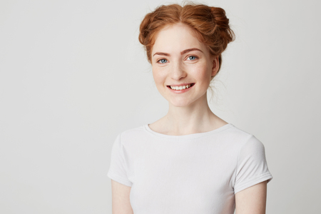 Young cheerful happy ginger girl with buns and freckles smiling looking at camera over white background. Stock Photo
