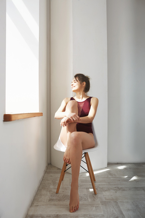 cheeful: Portrait of young happy beautiful model in swimwear sitting on chair looking at window enjoying morning sunlights over white wall.