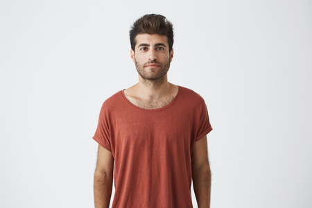 Portrait of stylish bearded guy with trendy haircut wearing casual red T-shirt looking with his brown eyes at the camera. Young handsome man having pleased look. People and emotions concept Stok Fotoğraf