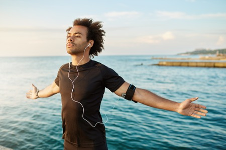 Sporty afro-American man stretching his arms before outdoor workout. Slim and strong male athlete wearing black T-shirt, keeping his arms open, breathing fresh sea air. Doing yoga at seaside Archivio Fotografico