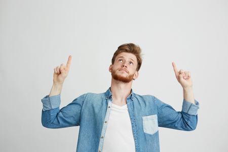 Portrait of cheerful young handsome man smiling pointing finger up over white background.