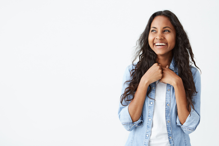 Portrait of charismatic and charming African-American woman with long wavy hair wearing stylish denim shirt, smiling widely, being excited to get surprise from her boyfriend, looking happy. Stock fotó
