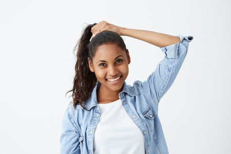 Pretty girl with dark skin smiling joyfully tying her long black wavy hair in ponytail, getting ready before going out with friends. Young African-American female model posing in studio. Stock Photo