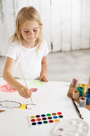 Playful, adorable little blonde girl with freckles in white cloth drawing ?louds and flowers on the white sheet of paper. Creative child sitting at the desk with watercolour pallet and brushes on it.