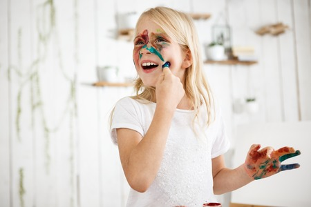 Playful seven-year-old blonde girl touching her face with finger in paint. Little girl painted her face with different colours. Playing kid. Stock Photo