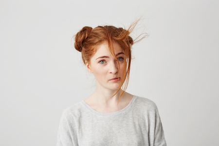 Portrait of young beautiful redhead girl with spoiled hair bun over white background. 版權商用圖片
