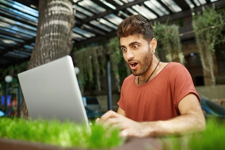 Shot of shocked bearded young man with dark hair and popped eyes, opened mouth dressed in red t-shirt looking at the screen of his notebook recieving e-mail with important news. Stock Photo